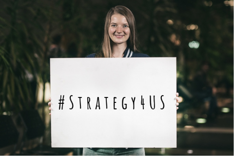 Girl holding a white card with the words: # Strategy4US